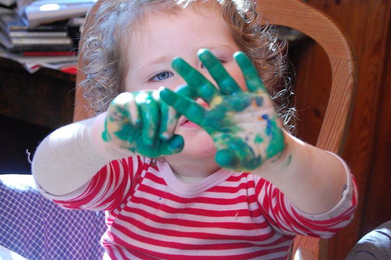 Kind mit grüner Fingerfarbe